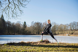 Woman doing stretching by frozen lake