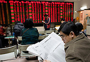 A man rads a newspaper as he monitors stock prices at a securities exchange in Beijing.