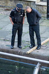 "© Licensed to London News Pictures . 06/10/2013 . Manchester , UK . Police look down as the lock is drained , to make the recovery . Police pull a body from The Bridgewater Canal in Manchester , adjacent to the City's "" Gay Village "" . The body was spotted yesterday (6th October) afternoon and a cordon was erected as specialist police divers made the recovery . Photo credit : Joel Goodman/LNP"