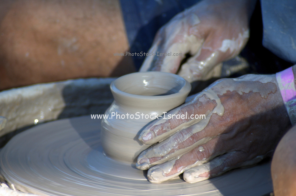 Man making a clay pot on a potters wheel