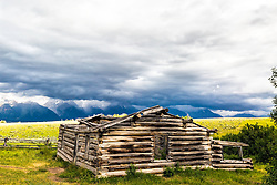 """Stormy day at the Shane Cabin of the movie """"Shane"""" fame.  The Grand Tetons of Jackson Hole are the mountains in the distance.  Grand Teton National Park<br /> <br /> For production prints or stock photos click the Purchase Print/License Photo Button in upper Right; for Fine Art """"Custom Prints"""" contact Daryl - 208-709-3250 or dh@greater-yellowstone.com"""