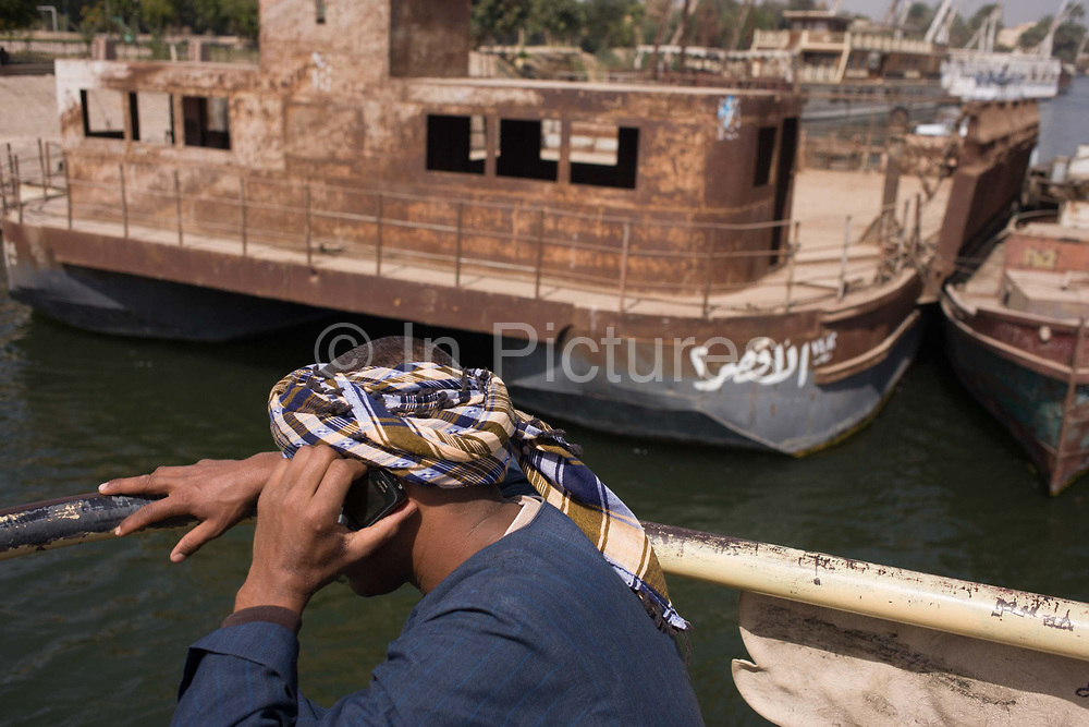 A local man talks on his mobile phone on the top deck of the state-run ferry across the River Nile at Luxor, Nile Valley, Egypt. Looking over his shoulder we see him holding his phone, not the latest model, to his ear as the boat approaches the pier on the West Bank where rusting wrecks are moored.