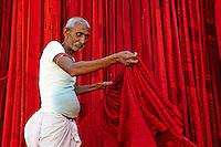 Inde, Rajasthan, Usine de Sari, Mango Singh, 60 ans. Les tissus sechent en plein air. Ramassage des tissus secs par des femmes et des enfants avant le repassage. Les tissus pendent sur des barres de bambou. Les rouleaux de tissus mesurent environ 800 m de long. . // India, Rajasthan, Sari Factory, Mango Singh, 60 old. Textile are dried in the open air. Collecting of dry textile  are folded by women and children. The textiles are hung to dry on bamboo rods. The long bands of textiles are about 800 metre in length.