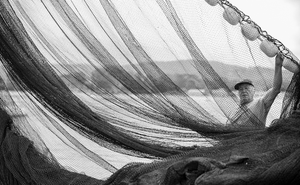 Clay, decades-long fisherman organizes squid nets on the commercial wharf in Monterey, Calif on May 13, 2021.