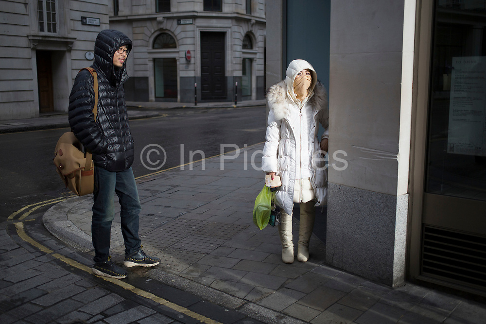 A Chinese woman tries to disguise her identity on a street corner, seriously claiming to be famous. UK.