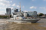 The Archer-class patrol and training vessel of the British Royal Navy, HMS Exploit P167 sails past City of London skyscrapers on the River Thames in London, England on July 06, 2018