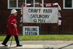 A voter leaves Trumpington village hall in Cambridgeshire, as voters cast their ballots in local council elections.