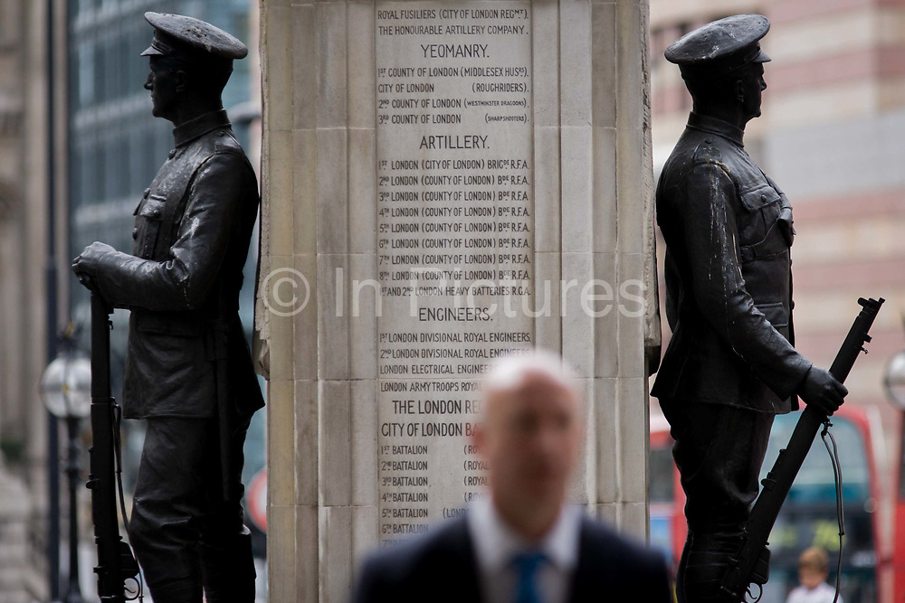 Modern man and a lost generation of youth. In the 100th year after WW1 started, the war memorial heroes in Cornhill, City of London remembering those killed in the First World War, lost in the trenches and the fields of Flanders from 1914-19. Dedicated by the City of London, the UK capital's financial and historic heart. Two soldiers face away from each other with rifles between their boots, they represent a lost generation when the nation's youth sacrificed their lives in the 20th century's first great conflict. The inscription says that their names will live for evermore.