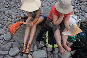 Mother and daughter read holiday novels on smooth pebbles at Trentishoe Cove, north Devon.