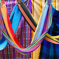 South America, Ecuador, Otavalo. Textiles. cloths, blankets, scarves, and hammocks hang on display at the Otavalo Market.