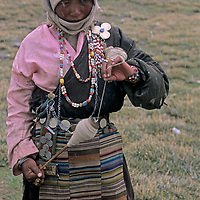 A nomadic Tibetan woman, dressed in her finest jewelry, spins wool during a snowstorm south of Lhasa.