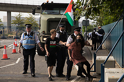 Metropolitan Police officers try to remove a human rights activist from the road in front of a large military vehicle during a protest against the DSEI 2021 arms fair at ExCeL London on 6th September 2021 in London, United Kingdom. The first day of week-long Stop The Arms Fair protests outside the venue for one of the world's largest arms fairs was hosted by activists calling for a ban on UK arms exports to Israel.
