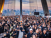 05 DECEMBER 2016 - BANGKOK, THAILAND: People sit on the deck of Bhumibol Bridge and wait for a ceremony honoring the late king to start. Tens of thousands of Thais gathered on Bhumibol Bridge in Bangkok Monday to mourn the death of Bhumibol Adulyadej, the Late King of Thailand. The King died on Oct 13 after a lengthy hospitalization. December 5 is his birthday and a national holiday in Thailand. The bridge is named after the late King, who authorized its construction. 990 Buddhist monks participated in a special merit making ceremony on the bridge.       PHOTO BY JACK KURTZ