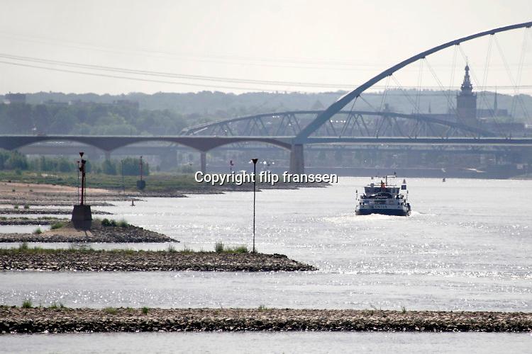 Nederland, Slijk-Ewijk, 26-5-2020 Het water in de waal zakt langzaam vanwege de aanhoudende droogte in haar stroomgebied.  Binnenvaartschepen varen richting Nijmegen onder de brug de Oversteek .  Langzaam daalt het peil van het water in de rivier In de herfst van 2018 stond de stand bij Lobith op 6,55 meter boven nap, een laagwater record dat veel overlast voor de binnenvaart opleverde .. . Die stand is nu nog 7,80 meter . In de maas wordt vanaf zuid Limburg het waterpeil kunstmatig geregeld via de stuwen en sluizen en is pas bij minimale aanvoer vanuit belgie grote verlaging zichtbaar. Foto: Flip Franssen