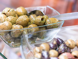 Green and black olives in glass bowl