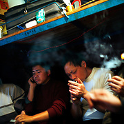 """Jeans workers smoke in their dormitory at Mr Yang's factory in Zhongshan city, China. .This picture is part of a photo and text story on blue jeans production in China by Justin Jin. .China, the """"factory of the world"""", is now also the major producer for blue jeans. To meet production demand, thousands of workers sweat through the night scrubbing, spraying and tearing trousers to create their rugged look. .At dawn, workers bundle the garment off to another factory for packaging and shipping around the world..The workers are among the 200 million migrant labourers criss-crossing China.looking for a better life, at the same time building their country into a.mighty industrial power."""