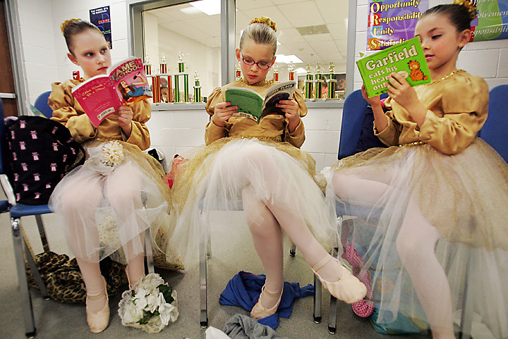 """galmh """"Nutcracker""""---From left, Samantha Priddy, Elizabeth Lewis and Hannah Smith enjoy some books while waiting for their turn to hit the stage in Columbia City Ballet's performance of Nutcracker in Clover."""