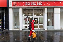 Glasgow, Scotland, UK. 21 November 2020. Views of Saturday afternoon in Glasgow city centre on first day of level 4 lockdown. Non essential shops and businesses have closed. And streets are very quiet. Pictured; Man dressed as Santa Claus walks in front of closed  down Christmas store called Ho Ho Ho   .Iain Masterton/Alamy Live News