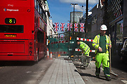 Workers sweep up as improvements take place underneath Union Jack flags in central London on Oxford Street, UK. This is the most famous street in the UK for shopping and mid range retail, and is consequently one of the busiest shopping streets in the country. As Britain prepares for the Queen's Diamond Jubilee and the London 2012 Olympics, the scenes of national pride are becomming common.