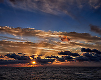 Sunrise, sunburst, crepuscular rays, and clouds over the Pacific Ocean from the aft deck of the MV World Odyssey. Image taken with a  Fuji X-T1 camera and 23 mm f/1.4 lens (ISO 200, 23 mm, f/16, 1/60 sec). Raw image processed with Capture One Pro.