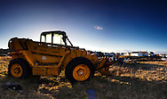 Easdale Island, Scotland. Telescopic Tractor with cottages in background.