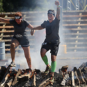 Kristiana and Robert Toschev in action at the fire jump obstacle during the Reebok Spartan Race. Mohegan Sun, Uncasville, Connecticut, USA. 28th June 2014. Photo Tim Clayton