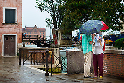 Tourists consult their map in the rain, Dorsoduro, Venice, Italy.<br /> Photo: Ed Maynard<br /> 07976 239803<br /> www.edmaynard.com