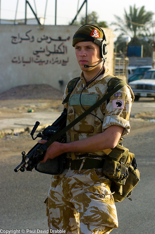 British soldiers from the Duke of Wellington's Regiment wearing desert camouflage, and body armor, carrying MiniMi Mini Machine gun Patrol through the streets of Basra city providing a security cordon for engineers who are doing a search for Improvised Explosive Devices also known as IED's  during Op-Telic in March 2005.