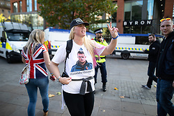 © Licensed to London News Pictures . 20/10/2018 . Manchester , UK . An EDL supporter wearing a t-shirt in support of Tommy Robinson (real name Stephen Yaxley-Lennon ) in Piccadilly Gardens . Street protest movement , the English Defence League ( EDL ) , hold a demonstration , opposed by anti-fascists , including Unite Against Fascism ( UAF ) , in Manchester City Centre . Amongst the reasons for their protest , the EDL cite news reports that revealed an imam at the Didsbury Mosque where Manchester Arena bomber Salman Abedi prayed , praised armed jihad in a sermon delivered just days before Abedi bought a ticket for the Ariana Grande concert at which he killed twenty two people . Photo credit : Joel Goodman/LNP