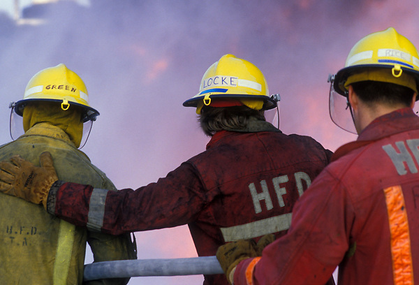 Three fire fighters from the Houston Fire Department extinguishing a fire