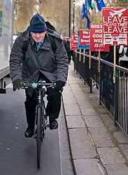 © Licensed to London News Pictures. 03/04/2019. London, UK. Boris Johnson MP cycling through Westminster past anti-Brexit placards. Yesterday evening British Prime Minister Theresa May made a statement in Downing Street offering to go into talks with Leader of the Labour Party Jeremy Corbyn, following the announcement of a request for an extension to article 50, thereby delaying Britain leaving the European Union. Photo credit : Tom Nicholson/LNP