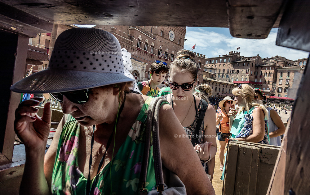 """Italy, Siena, the Palio: tourist going in and out the Piazza del campo passing throw the narrows wooden Seats called """"Palchi"""" (all around the square)"""