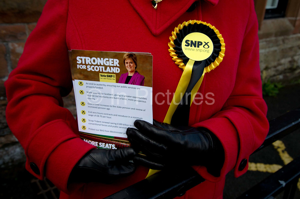 General election 2015. West Kilbride, Scotland. Observer at polling place from SNP party wearing a rosette and holding leaflet supporting Nicola Sturgeon.