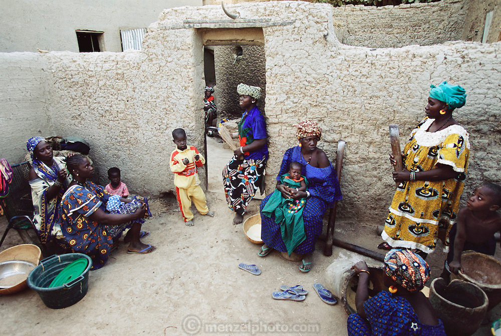 Pama Kondo (in yellow) talks with family members and friends in her courtyard as her daughter Pai gets her hair styled for her wedding. Pai, 18, will be married today to her first cousin, Baba Nientao, who has come back from the Ivory Coast where he has lived with his family since he was 12 years old. The arranged marriage was revealed to Pai this morning, as is the custom, and she is quiet as part of the ritualized mourning for her lost youth.