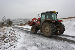 © Licensed to London News Pictures. 13/02/2021. Hundred House, Powys, Wales, UK. A tractor is seen in a bitterly cold landscape as strong south east winds and snow hit Mid Wales with temperatures minus 2.5 deg C and 'feels like' temperature around minus 5 deg C near Hundred House in Powys, Wales, UK. Photo credit: Graham M. Lawrence/LNP