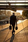 Man carrying brief cases walking under Millennium Bridge on Southbank, London, England, UK