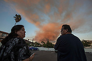 People watch as a smoke plume from a brushfire rises in San Gabriel Canyon above Azusa, California, Monday, September 23, 2013.  A fire that began above Azusa burned north into the Angeles National Forest and was growing. The fire started at 5:56 p.m. and county firefighters fought the blaze with SuperScoopers, helicopters and ground forces.  (Photo by Ringo Chiu/PHOTOFORMULA.com)