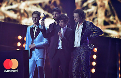 The 1975's Matthew Healy, Adam Hann, George Daniel and Ross MacDonald with their award on stage at the Brit Awards at the O2 Arena, London.
