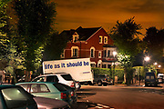 A white catering van with the brand logo of 'Life as it should be' is parked in a residential area in north London at midnight. The cars are well lit by bright streetlamps in Highgate Village.