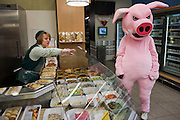 Moscow, Russia, 03/03/2011..A shop assistant directs a demonstrator in a pig costume as members of health campaign group Pigs Against check the sell-by dates and quality of food in a city centre supermarket while dressed as pigs.