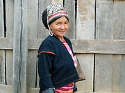 An Akha ethnic minority woman wearing traditional clothing made from home grown, indigo dyed cotton outside her home, Ban Lakham, Luang Namtha province, Lao PDR. One of the most ethnically diverse countries in Southeast Asia, Laos has 49 officially recognised ethnic groups although there are many more self-identified and sub groups. These groups are distinguished by their own customs, beliefs and rituals.