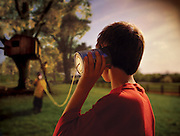A boy holds a can attached to a string up to his ear, playing telephone with his friends at their treehouse