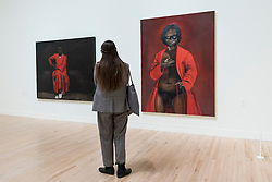"© Licensed to London News Pictures. 02/12/2020. LONDON, UK. A visitor views (L to R) ""First"", 2003, and ""Any Number of Preoccupations"", 2010.  Preview of ""Lynette Yiadom-Boakye: Fly In League With The Night"" the first major UK survey exhibition by British artist Lynette Yiadom-Boakye.  Over 70 of her works spanning two decades are on display at Tate Britain.  It is the first new exhibition at Tate since the galleries were re-opened after coronavirus lockdown restrictions were slightly eased by the UK government.  Photo credit: Stephen Chung/LNP"