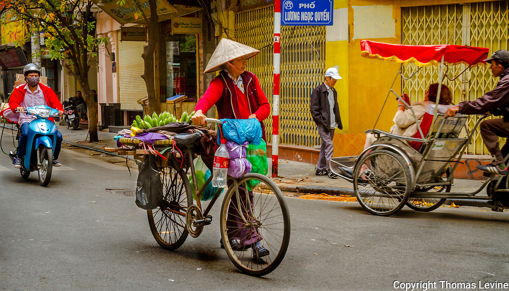 This Vietnamese Lady is walking her bicycle which is full of fruit around the Old Quarter selling her fresh fruit. RAW to Jpg