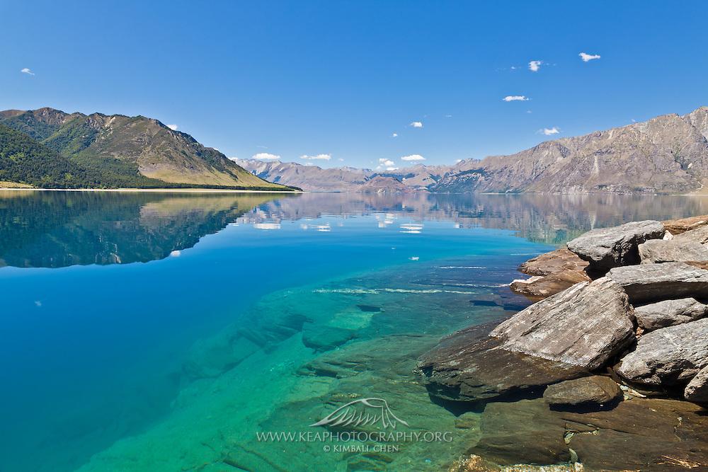 A sunny day illuminates the blue and green hues of Lake Hawea, Central Otago, New Zealand.