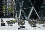With thousands of employees in the capitals financial district still working from home during the Coronavirus pandemic, other City workers enjoy a socially distanced lunch beneath the Swiss Re building aka the Gherkin, on 29th July 2020, in London, England.
