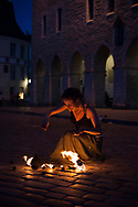 Tallinn, Estonia - July 27, 2015: A young woman from St. Petersburg, Russia, dances with fire for tips in the main square Raekoja Plats in the Old Town of Tallinn, Estonia.