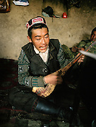 Samar Khan playing traditional Komuz at the campment of Tash Seri..Winter expedition through the Wakhan Corridor and into the Afghan Pamir mountains, to document the life of the Afghan Kyrgyz tribe. January/February 2008. Afghanistan