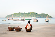 Myanmar, Ngapali. Man waits at the beach with two empty baskets.<br /> Every single morning all the fisherman from the little village at Ngapali Beach come back home with their night catch. At the beach all the women wait for them and afterwards work with drying and selling fish and other creatures from the sea begins.