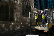 Workmen loading a lorry within street scene of light and shadow in the City of London, England, United Kingdom.